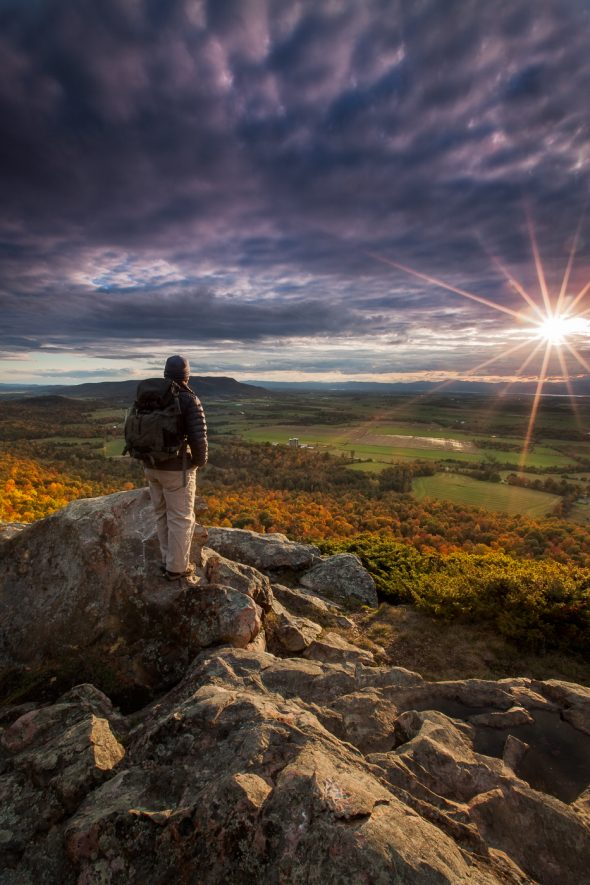 photographer standing on top of mountain at sunset