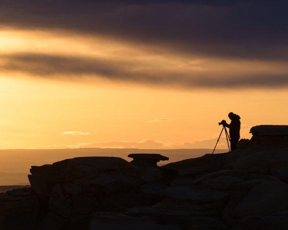 Photographer against a vibrant sunrise sky
